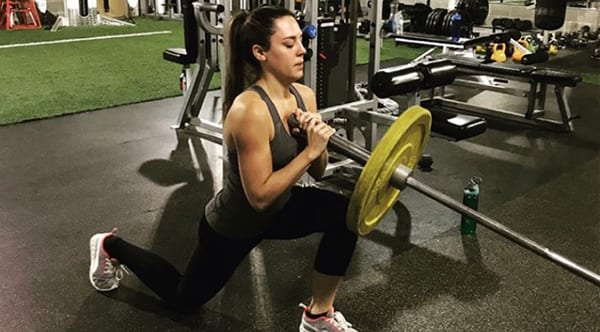 Megan, a former patient of Dr. Jay Granzow, MD, works out lifting weights at the gym.