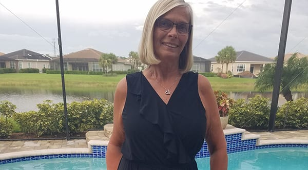 Cindy standing by her pool at home after successful SAPL surgery with Dr. Jay Granzow, MD.