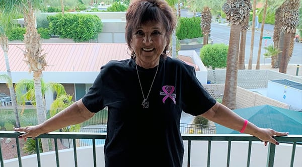 Carol, a former patient of Dr. Jay Granzow, MD, stands on her balcony overlooking palm trees.