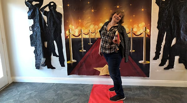 Keli, a former patient of Dr. Jay Granzow, MD, stands on a red carpet with an award in hand at an event.