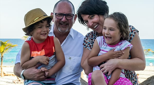Danielle, a former patient of Dr. Jay Granzow, MD, smiles while holding her daughter and sitting next to her husband and son at the beach.