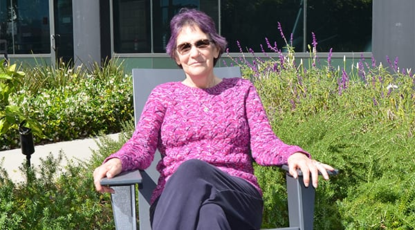 Sarah, a former patient of Dr. Jay Granzow, MD, sits outside in the sun in front of a garden.