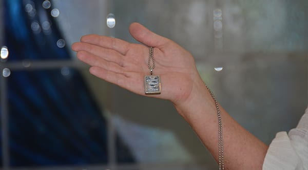 Christine, a former patient of Dr. Jay Granzow, MD, holds out a necklace that says