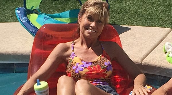 Cynthia, a former patient of Dr. Jay Granzow, MD, sits on an inflatable chair floating in a pool with her legs exposed.